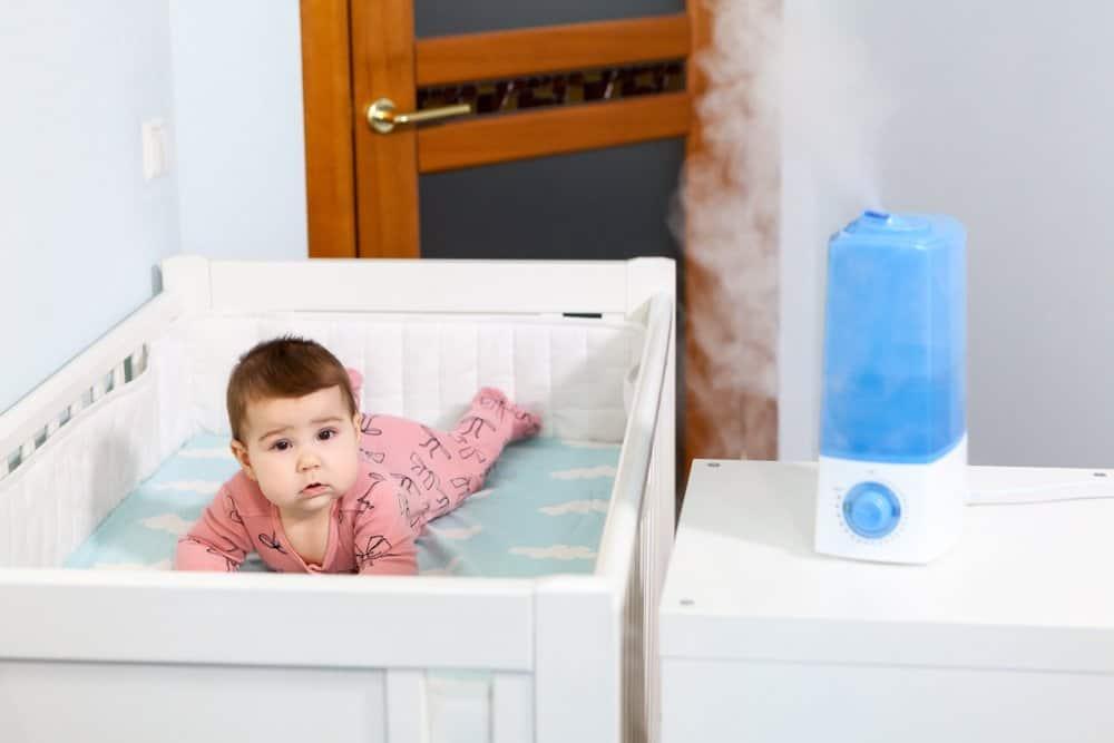 嬰兒床裡的嬰兒,旁邊的櫃檯上放著加濕器